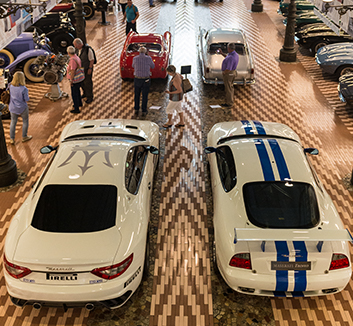 Modern race cars sit alongside older Maserati racers
